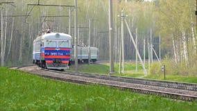 El tren de pasajeros pasa y entra lejos en bosque almacen de metraje de vídeo