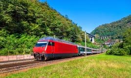 El tren de pasajeros va abajo del paso de Gotthard - Suiza Imágenes de archivo libres de regalías