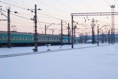 El tren de pasajeros viaja a través de los carriles nevados Foto de archivo