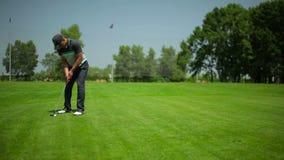 El tren del hombre para jugar a golf en el campo del golf metrajes