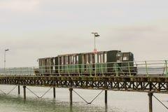 El tren del indicador estrecho que funciona con la longitud de los pasajeros que llevan del embarcadero de Hythe a y desde el tra Fotos de archivo