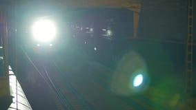 El tren eléctrico con las luces brillantes encendidas sale del túnel almacen de metraje de vídeo