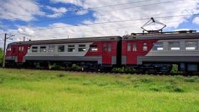 El tren eléctrico suburbano rojo y blanco brillante va cerca en ferrocarril almacen de video
