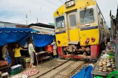 El tren pasa por el mercado de las vías ferroviarias de Mae Klong en Samut Songkram, Tailandia Foto de archivo libre de regalías