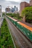 El tren rueda abajo las vías con el horizonte de Philadelphia Fotos de archivo