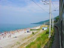 El tren va por el mar, una playa, gente Foto de archivo libre de regalías