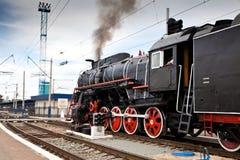 El tren viejo del vapor está saliendo de una estación Fotografía de archivo
