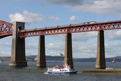 El tren y los barcos con adelante cercan el puente con barandilla, Escocia Foto de archivo libre de regalías
