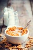 El trigo del cereal de desayuno forma escamas en las botellas de cerámica o del cuenco y de leche Foto de archivo
