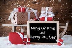 El trineo con los regalos, copos de nieve, manda un SMS a Feliz Año Nuevo de la Feliz Navidad Foto de archivo