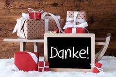 El trineo con los regalos en nieve, medios de Danke le agradece Foto de archivo