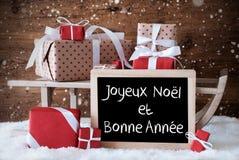 El trineo con los regalos, nieve, copos de nieve, Bonne Annee significa Año Nuevo Fotos de archivo libres de regalías