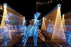 El trineo de la Navidad, los ciervos y el bokeh de los árboles se encienden Imágenes de archivo libres de regalías