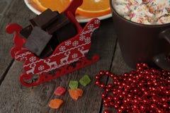 El trineo de Papá Noel rojo con el chocolate, cacao caliente con las melcochas, decoraciones de la Navidad Milagro de la Navidad  Fotografía de archivo