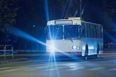 El trolebús va en la calle de la noche abajo Imagenes de archivo