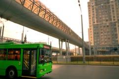 El trolebús verde monta en el camino en ciudad contra el contexto de edificios altos y en peatón superior Imagen de archivo