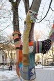 El tronco de árbol vistió arte del invierno de la gente del paño de las lanas imagen de archivo