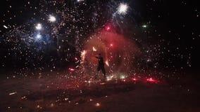 El truco mente-que sopla de un hombre en una demostraci?n del fuego en la noche ?l est? lanzando realmente chispas alrededor con  metrajes