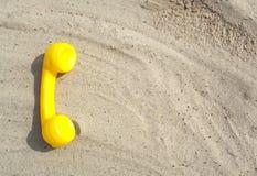 El tubo amarillo de un teléfono viejo está mintiendo en la arena con un espacio de la copia para su texto con los contactos foto de archivo