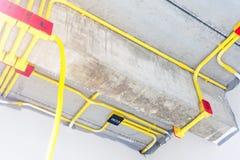 El tubo el?ctrico blanco del PVC en rojo y negro est? conectado con las l?neas el?ctricas o los alambres el?ctricos, los cables d imágenes de archivo libres de regalías