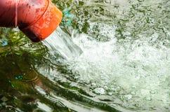 El tubo de agua coloca el agua en la charca Imágenes de archivo libres de regalías