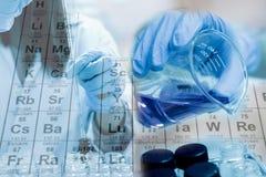 El tubo de ensayo y el cubilete en mano del científico con el equipo y la ciencia experimenta, reactivo químico del terraplén del Foto de archivo libre de regalías