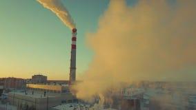 El tubo de la fábrica lanza mucha niebla con humo El humo considera hermoso pero peligroso la puesta del sol almacen de metraje de vídeo
