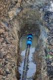 El tubo quebrado del pvc en foso se escapa el agua Foto de archivo