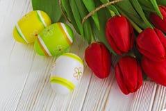 El tulipán rojo del ramo florece con los huevos de Pascua en la tabla de madera vieja Imagen de archivo