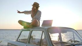 El turismo ecológico, muchacha se sienta en el tejado del coche en contraluz que habla en el arsenal solar del teléfono móvil y d