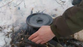 El turismo, un hombre pone las barras en el fuego, cocina la sopa en la campaña, almacen de video