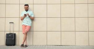 El turista africano joven está listo para un vuelo Él está escuchando la música y está charlando feliz en el teléfono móvil mient almacen de video