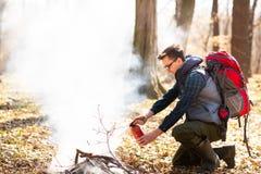 El turista apaga el fuego del extintor, despu?s de un resto en la naturaleza fotografía de archivo