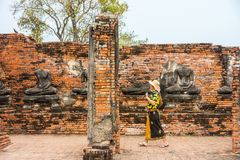 El turista asiático con las camisas florales coloridas va a hacer turismo en las ruinas de Wat Chaiwatthanaram Foto de archivo libre de regalías