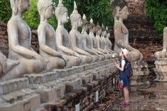 El turista asiático de la muchacha que sostiene un loto con el respeto o ruega fotos de archivo