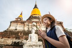 El turista asiático de la muchacha que sostiene un loto con el respeto o ruega en Wa fotos de archivo