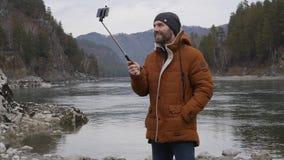 El turista barbudo está difundiendo el vídeo en un teléfono móvil en el banco de un río de la montaña Cámara lenta