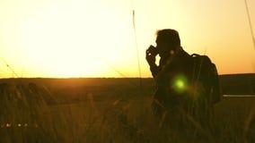 El turista bebe puesta del sol caliente del t? y de los relojes Resto despu?s de alcanzar la meta Viajero solo que se sienta enci metrajes