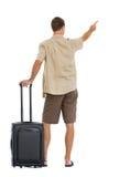 El turista con las ruedas empaqueta señalar en espacio de la copia Imagenes de archivo