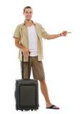 El turista con las ruedas empaqueta señalar en espacio de la copia Imagen de archivo libre de regalías