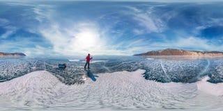 El turista con los trineos camina a lo largo del hielo azul del lago Baikal 360 grados esféricos 180 del panorama Fotografía de archivo