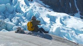 El turista con una mochila amarilla mira un glaciar hermoso piedras de los tiros abajo almacen de video