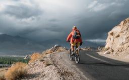 El turista de la bici monta en el camino de la montaña de Himalaya en manera al buddist m Fotografía de archivo