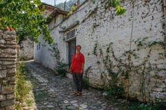 El turista de la chica joven en una blusa rosada se está colocando en un camino cobbled en la ciudad albanesa antigua de Berat fotografía de archivo libre de regalías