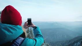 El turista de la chica joven hace la foto en smartphone en invierno Fotografía las montañas coronadas de nieve metrajes