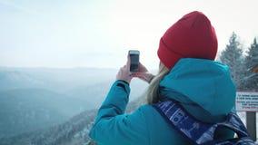 El turista de la chica joven hace la foto en smartphone en invierno Fotografía las montañas coronadas de nieve almacen de metraje de vídeo