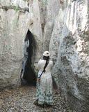 El turista de la hembra hace frente a una entrada a una cueva foto de archivo libre de regalías