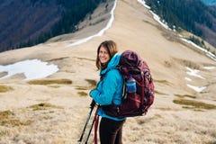 El turista de la muchacha con la mochila es montañas que viajan fotos de archivo libres de regalías