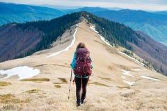 El turista de la muchacha con la mochila es montañas que viajan imagenes de archivo