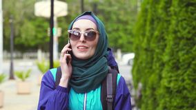 El turista de la muchacha en un pañuelo y las gafas de sol en una mochila que hablan en el teléfono reducen el MES almacen de metraje de vídeo